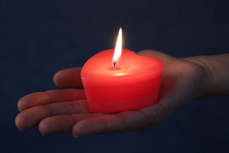 bougie coeur: Burning red heart candle in a hand. Light of love in the dark