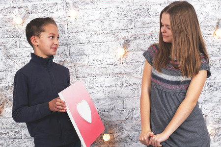 Happy Valentines Day. Young boy giving a heart picture to his girlfriend