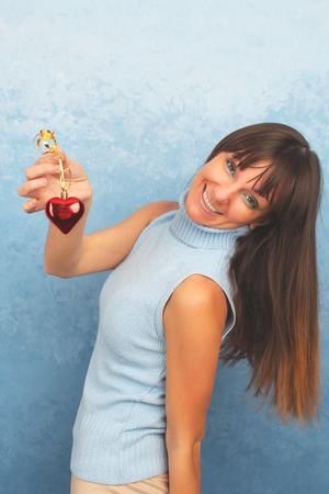 Smiling young Lady in light blue with a red heart decoration
