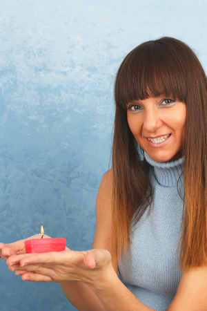 Young woman with burning red candle in her hands Reklamní fotografie