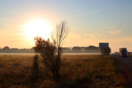 Dawn outside the city. Autumn begins. A huge sun rises over the yellowed grass. Morning fog. There are cars and trucks on the road