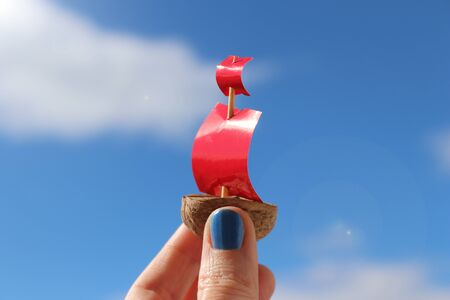Small toy boat made of walnut with red paper sails in hand. Blue sky with clouds. Banque d'images - 132919967