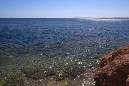 Transparent waters of Red Sea. Rocky shore. Water glistens in the sun. Horizon. Freedom