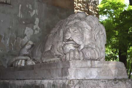 White stone statue of a sleeping lion. Ancient monument of architecture. Beautiful texture for a computer game Banco de Imagens