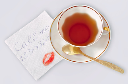 footsie: Cup of tea and napkin with a text Call me, a phone number and a kiss.