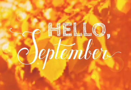 Hello, September! Blurred autumn background with greeting inscription.