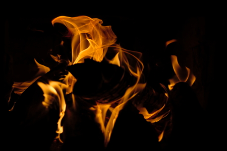 Flames on black background, burning firewood, orange flames highlighted