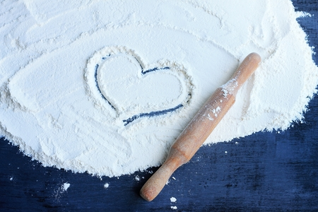 Heart drawn on flour on the table. There is a rolling pin near it. Concept of cooking with love. Top view.