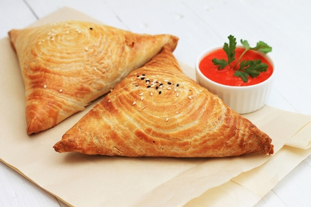 Samosa and sauce on white wooden background, Indian and eastern food.