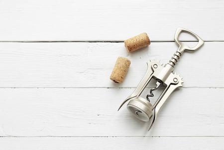 Metal corkscrew for wine and cork on white wooden background. Copyspsce. Archivio Fotografico - 124695112