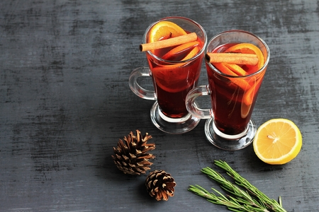 Sweet mulled wine for two person in glasses on a black background, decorated fir cones and rosemary. Copy space.