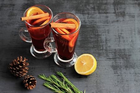 Sweet mulled wine for two person in glasses on a black background, decorated fir cones and rosemary. Copy space. Imagens - 124695115