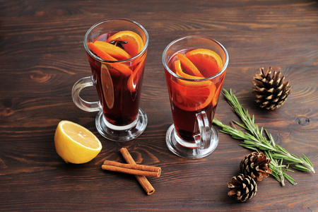 Two glasses of mulled wine with cinnamon, oranges, fir cones and rosemary on a brown wooden background.