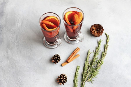 Two glasses of hot red mulled wine or gluhwein with orange, cinnamon sticks on light background. Spicy warm beverage. Seasonal mulled drink. Copy space.