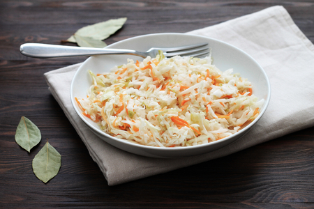 Fermented cabbage. Vegan food. Sauerkraut with carrot and spices in bowl on the dark background. Trend food. Typical fermented food in some countries such as Russia, Poland or German.