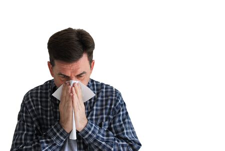 Adult man in a plaid shirt with handkerchief. Sick man isolated has runny nose, man makes a cure for the common cold. Copy spase.