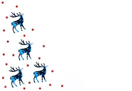 Christmas and New Year background with blue silhouette deer and reds stars confetti, decoration. Holiday symbols on white background. Copy space.