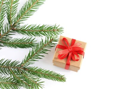 Gift box with a Christmas present on white background and branch spruce. Top view, copy space.