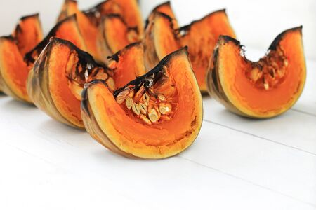 Close up of baked pumpkin slices on white wooden background. Healthy vegetarian, vegan food.