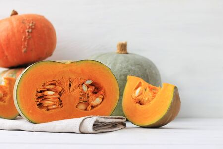 Group of halves and whole pumpkin on a light wooden background. Pumpkin is not cleared of seeds. Place for text.