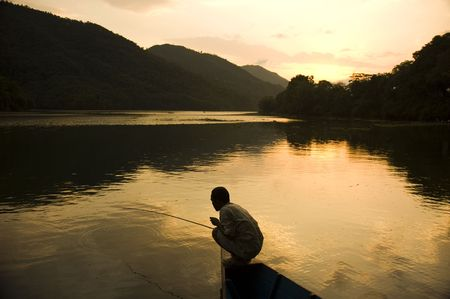 punting: silhouette of a man fishing