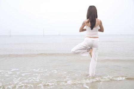 asian girl performing yoga on a beach Stock Photo - 5781173