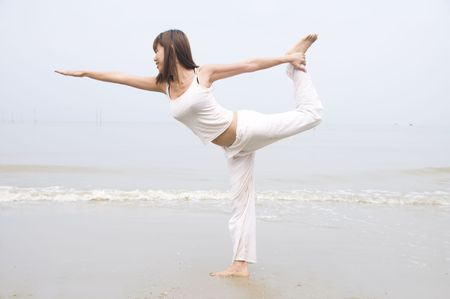 asian girl performing yoga on a beach Stock Photo - 5781175