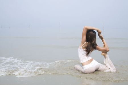 asian girl performing yoga on a beach photo