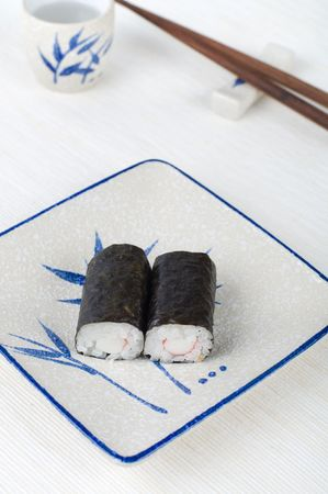makki: sushi on a plate with chopstick and tea cup