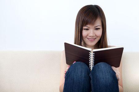 Women Reading a Book on Sofa photo
