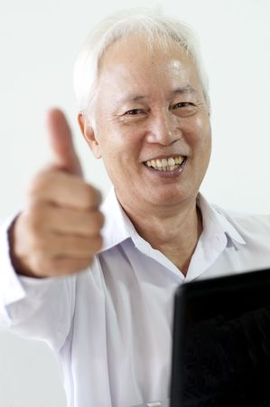 malaysian: senior asian business man with laptop and thumbs up