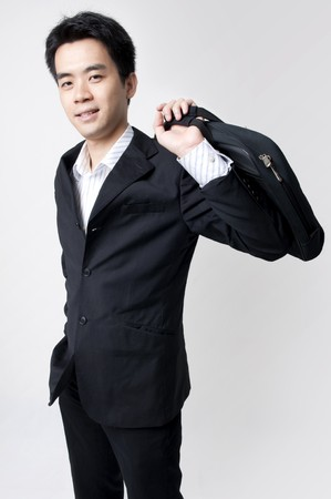 young male executive holding a business bag and smiling photo