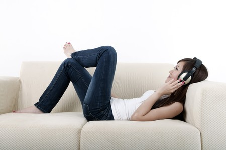 beautiful young asian listening to music on a sofa photo