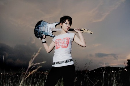 grunge style rock asian female  with a guitar ,girl wearing generic shirt  photo