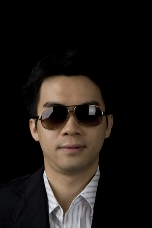 young asian businessman with dark glasses and black background photo