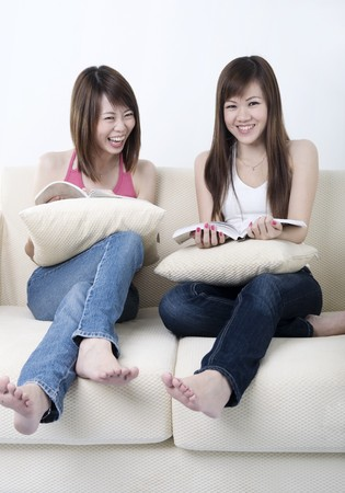 two friends talking: young asian girl sitting on sofa and chatting