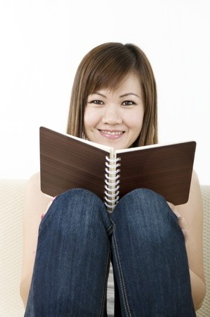 asian girl reading and sitting on a sofa  photo