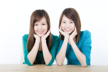 hand on chin: two asian adults sitting on a table and smiling Stock Photo