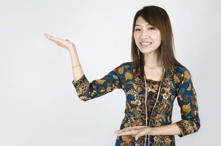 batik: fille asiatique sur une combinaison de batik tout en posant un signe de bienvenue  Banque d'images