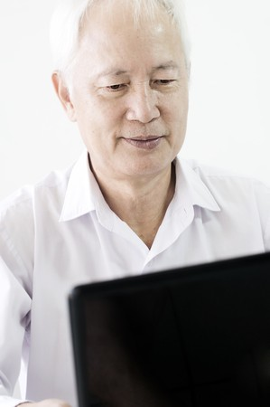 old asian business man surfing with a laptop photo