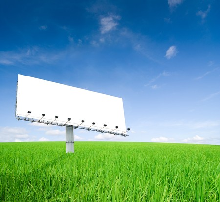 an empty billboard on a green field photo
