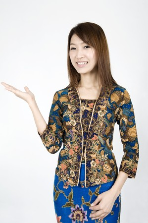 indo: asian girl wearing a batik outfit with hands facing up