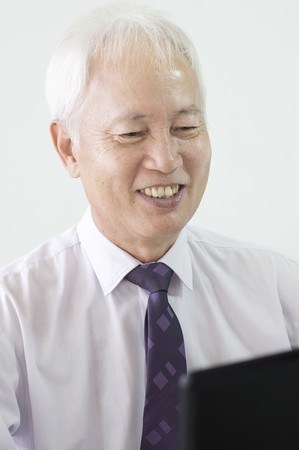 old asian business man smiling and using a laptop   photo