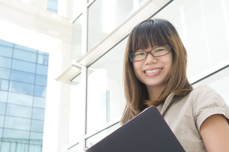 asian business women: young asian business women holding a folder and smiling