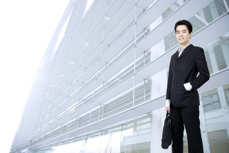 young asian business man holding a suitcase with office background  photo