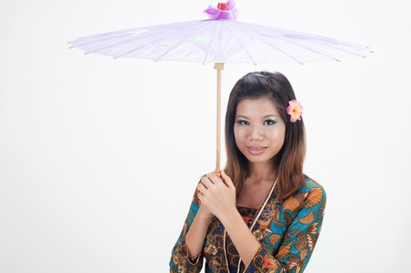 Portrait of a woman with kebaya with umbrella on white background  photo