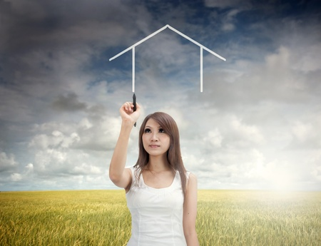 dream land: asian girl drawing a dream home during early morning