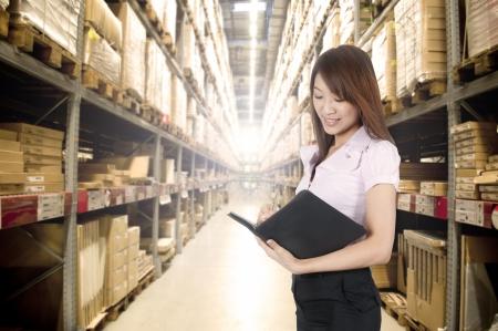 warehouse interior: ragazza asiatica stock contando in magazzino Archivio Fotografico