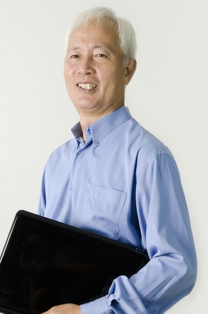 asian man face: senior asian business man holding a laptop and msiling  Stock Photo