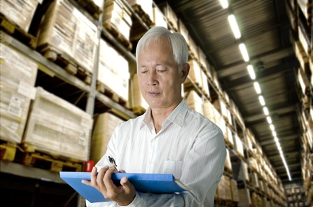 senior asian business man doing stock count in a warehouse photo
